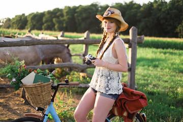 Woman Sitting on a Bike Holding Camera