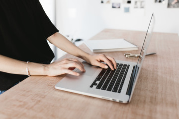 female artist designer working on laptop computer in bright studio