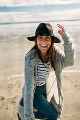 Beautiful young woman walking and playing on the beach wearing gumboots