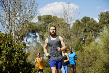 Fit Man With Friends Running On Sunny Day