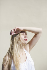 Blonde girl with arm raised for sun protection