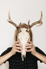 person holding deer skull in front of face with both hands