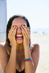 Smiling woman taking a shower on the beach.