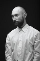 young white beard man white shirt black pants studio monochrome background