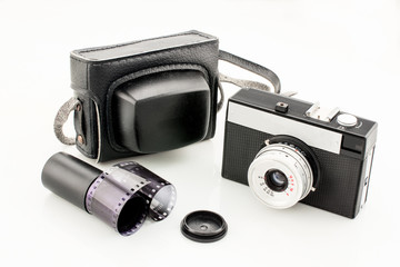Vintage camera, it's case and filmstrip on a white isolated background, analog photography concept