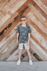 Boy wearing mirrored sunglasses standing against wall