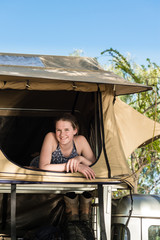 teen girl inside a roof top camping tent