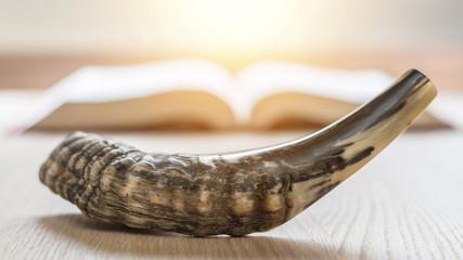Yom Kippur and Rosh Hashanah (Hashana)  (jewish New Year holiday) concept with Ram shofar (horn) with religious holy prayer book on table