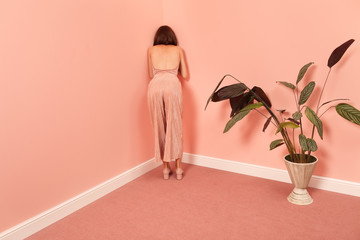 fashionable woman leaning against a pink wall