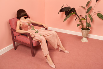 woman sitting on an armchair in a pink room