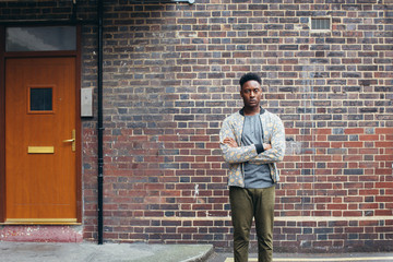 London Street Style - Outdoor Portrait of Young Casual Black Man Standing in Front of Working Class Home