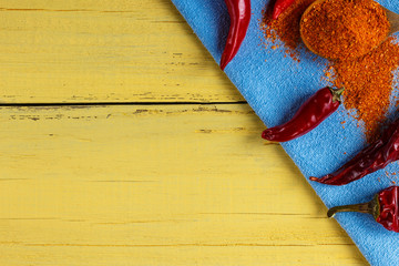 Red pepper fresh, dry and ground, on a wooden yellow background, the top view.