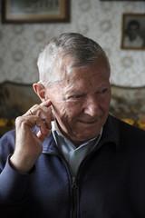 Portrait of a senior man adjusting his hearing device