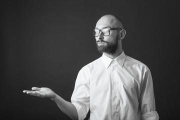 young white beard wearing glasses man white shirt black pants studio monochrome background hand out placeholder