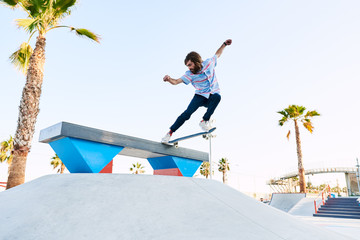Bearded skater performing trick in skate park with arms widened
