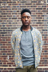 London Street Style - Outdoor Portrait of Young Casual Black Man Standing in Front of Exposed Brick Wall