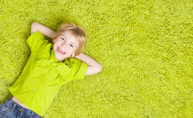 Child Lying Over Green Carpet. Happy Smiling Kid, Boy Five Years Old, Top View