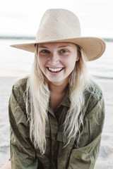 Young woman at the beach wearing a straw hat