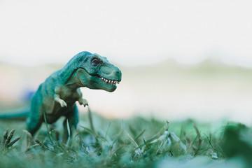 Green toy dinosaur on grass