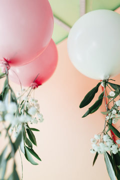 Balloons decorated with flowers and leafs by the ceiling of a room