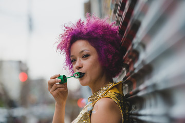 Young woman with pink afro in the city