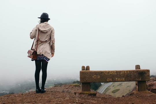 Unrecognizable woman in hat and coat against of foggy San Francisco