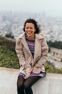 Laughing young brunette with eyes closed in wind