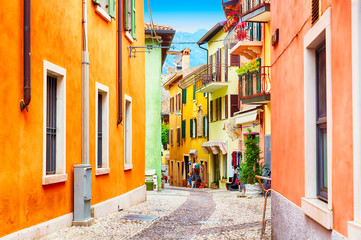Small town narrow street view with colorful houses in Malcesine, Italy during sunny day. Beautiful...