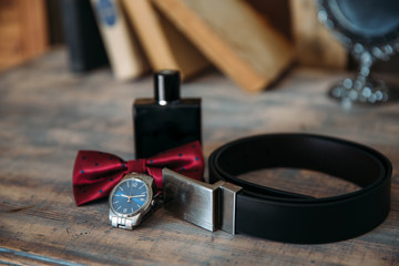 Wedding groom accessories, details of clothes, belt, wristwatch, boutonniere, bow-tie, perfume.