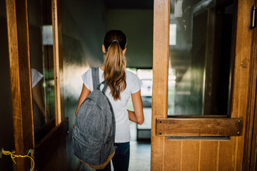 Young girl with ponytail and backpack going to school