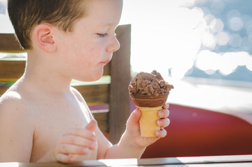 Little boy eating an ice cream cone in summer