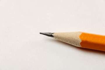 Sharpened pencil on a white blank sheet of paper, macro shot