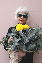 Trendy and attractive older female holding a bunch of colourful flowers