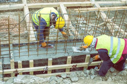 Builders crew leveling concrete footing pour 2