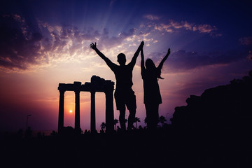 Silhouette of a happy group of friends backdrop of ancient ruins.