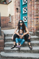 Mother and her long haired 6 years old daughter on their front porch