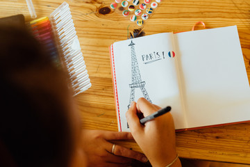 teen drawing Eiffel tower in journal