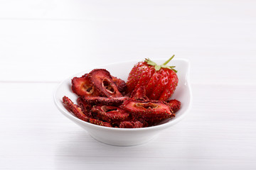 Fresh strawberry and dried strawberry slices on white wooden table.