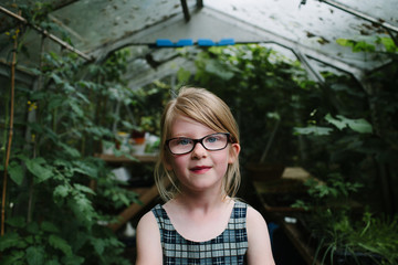 Portrait of young girl with long blonde hair and glasses standing in a greenhouse.