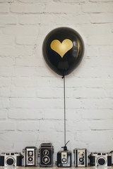 Black balloon decorated with golden heart and collection of old reflex cameras