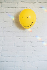 Smiling face painted on yellow balloon and rainbow lights