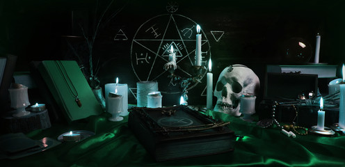 Witchcraft composition with burning candles, human skull, magic sphere, books, jewelry, tarot cards, chalk and pentagram symbol. Halloween and occult concept, black magic ritual.