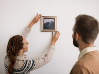 Couple hanging a picture in new home