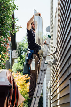Window Washer Removing Screen From Window While Standing On Ladd