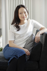 Portrait of asian woman sitting on a sofa in her modern home.
