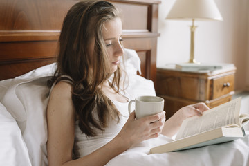 Beautiful girl reading book with cup of coffee