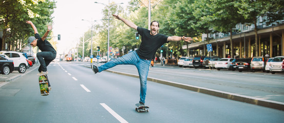 Two happy and funny skaters ride skateboard on city street