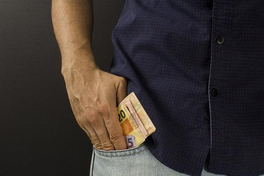 Man putting brazilian money inside the pocket