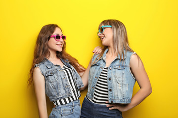 Portrait of two young woman with sunglasses on yellow background