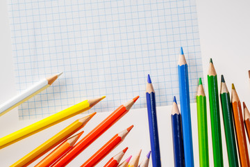 Color pencils on white background. Free space for text. Tools for drawing, education, school, creativity. Sheet of the notebook on the table.